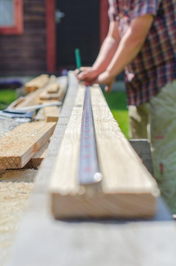 测量木板条的男性手 库存照片