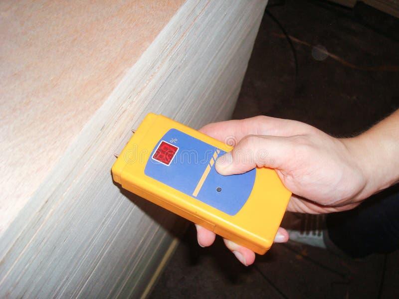 测量木湿气密度的水平质量管理的工作者 免版税库存照片