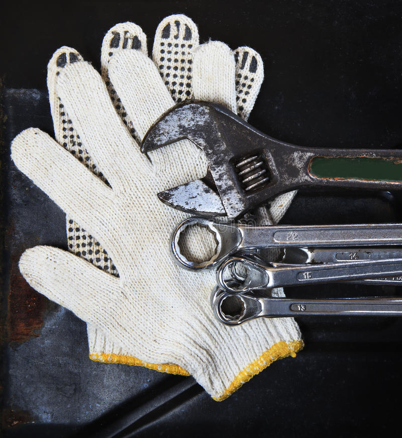 测量深度板钳的扳手和在黑暗的金属后面的技工手套 库存图片