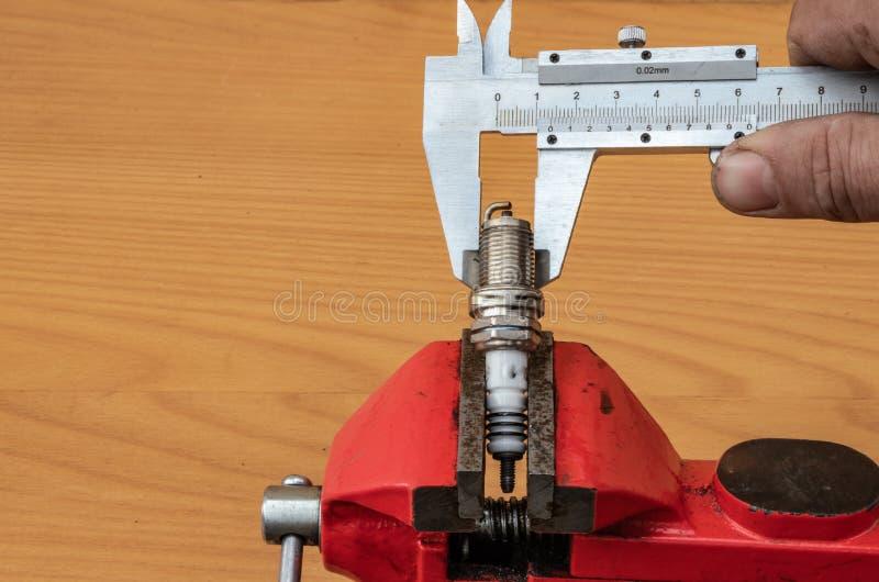 测量火花塞的直径技术使用轮尺的 库存照片