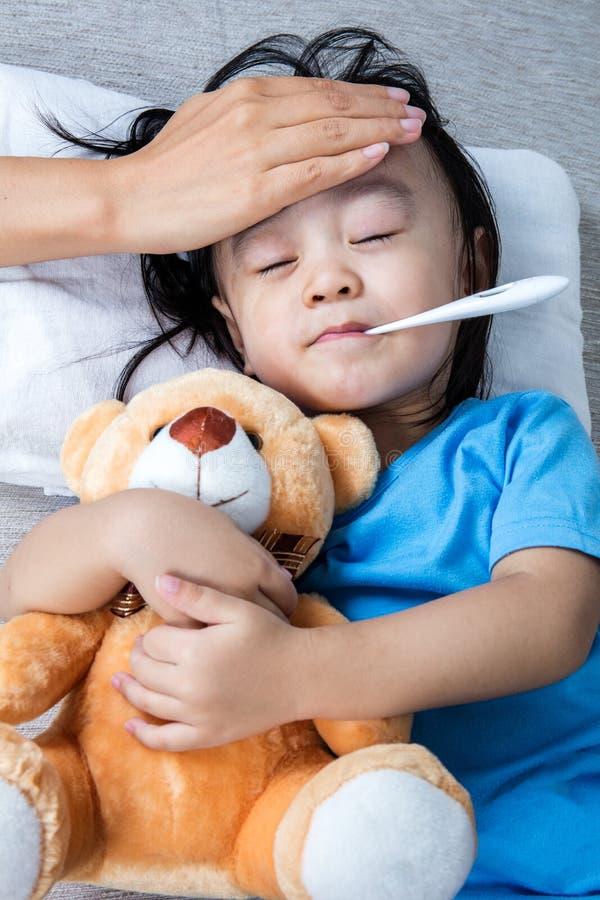 测量热病的亚裔中国母亲小女孩前额 免版税库存照片