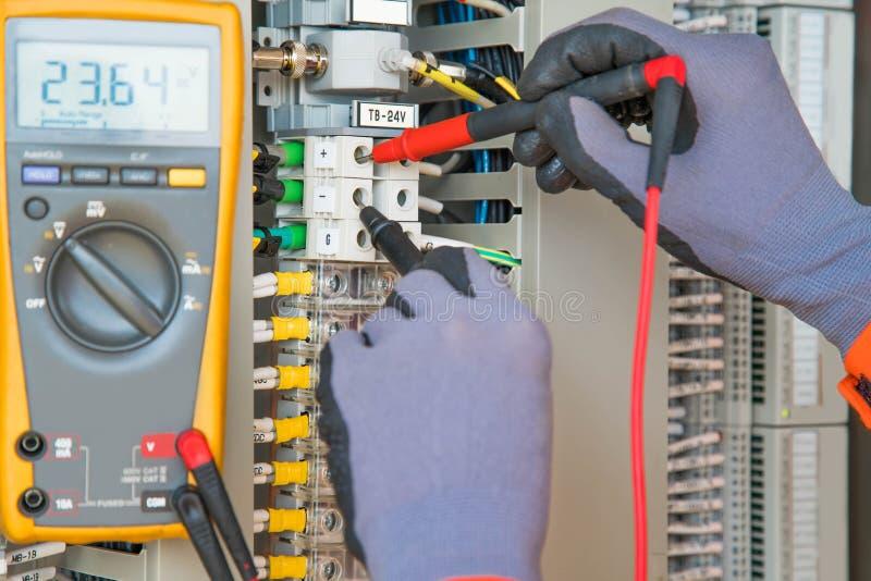 测量电压和检查电路的电工和仪器工作者佩带的安全手套通过使用智能数字仪表 免版税库存照片