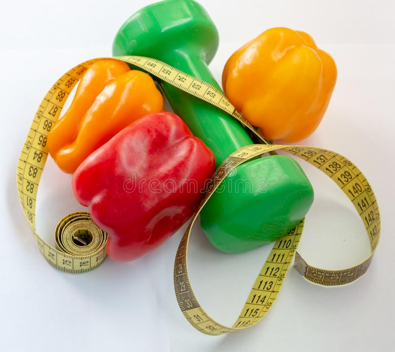 测量的磁带和胡椒在白色背景 健身哑铃 图库摄影