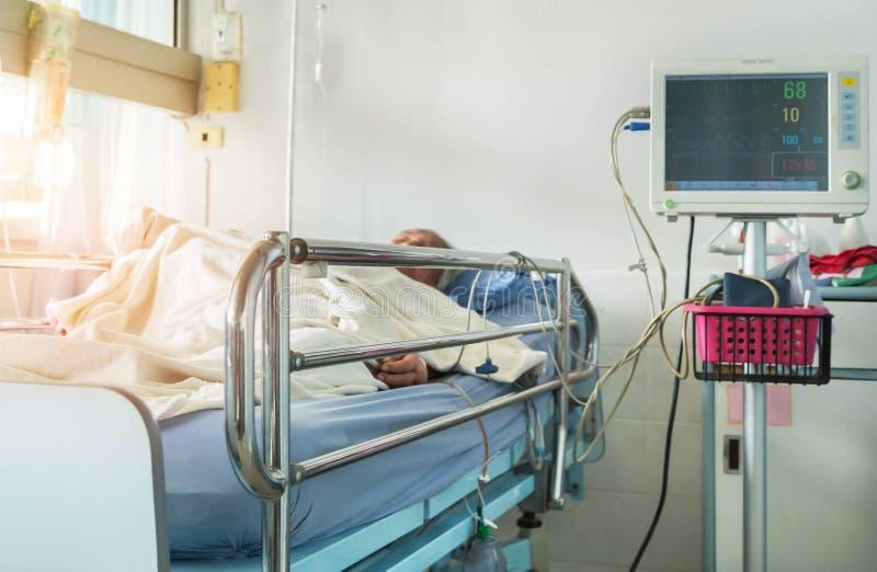 测量的血压显示器数字式设备与在床上的年长耐心睡眠在医院 图库摄影