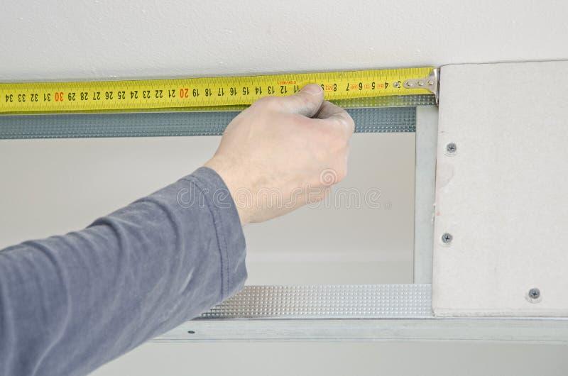 测量石膏的男性手 免版税库存照片