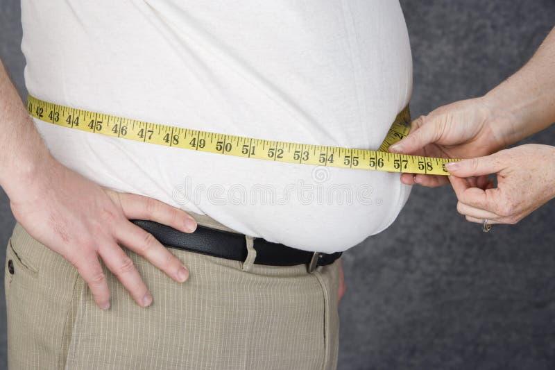 测量肥胖人的腹部的手 免版税库存图片