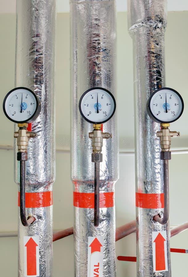 测量仪在热导管附近的锅炉室有绝缘材料涂层的 免版税库存照片