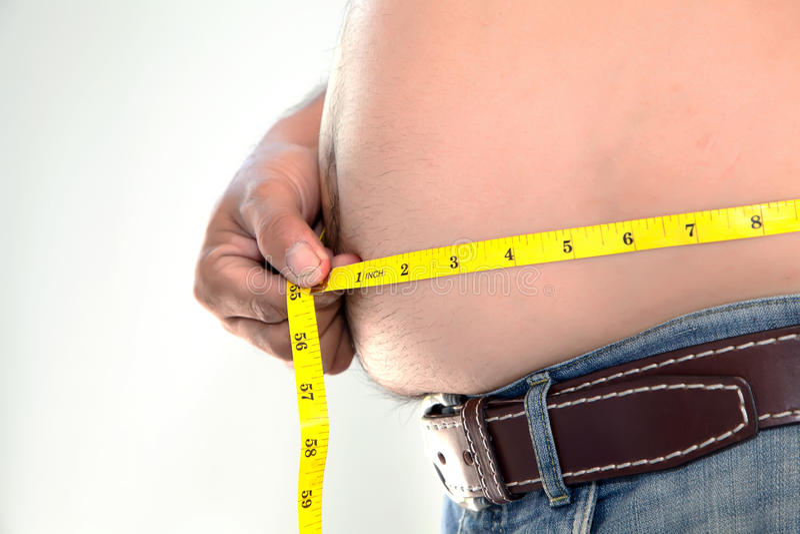 测量他的腹部的肥胖人 库存照片