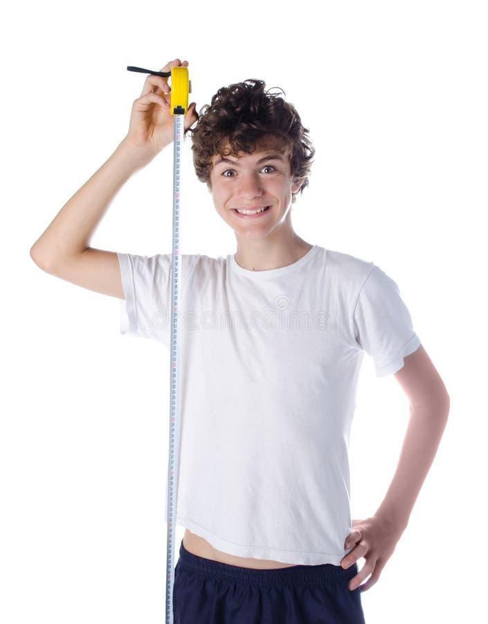 测量他自己的高度的愉快的男孩 库存图片
