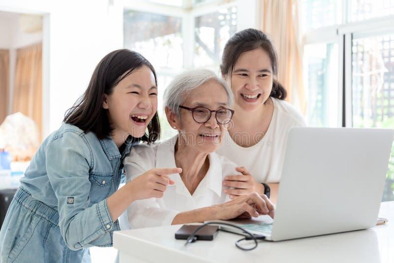 浏览互联网的母亲和女儿;观看事有趣与祖母,愉快的微笑的亚洲资深妇女一会儿 免版税库存图片