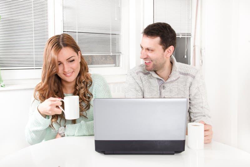 浏览互联网的笑的夫妇在膝上型计算机 免版税图库摄影