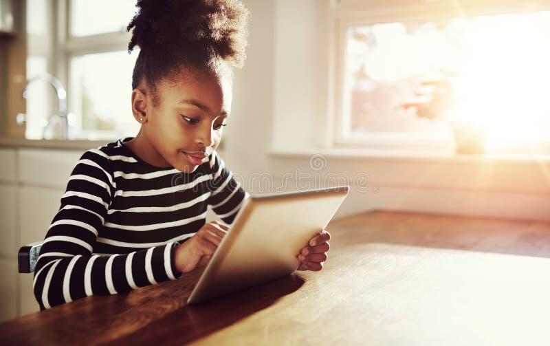 浏览在片剂个人计算机的年轻黑人女孩 免版税图库摄影