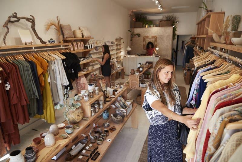 浏览在独立衣物和礼品店的顾客 免版税库存图片