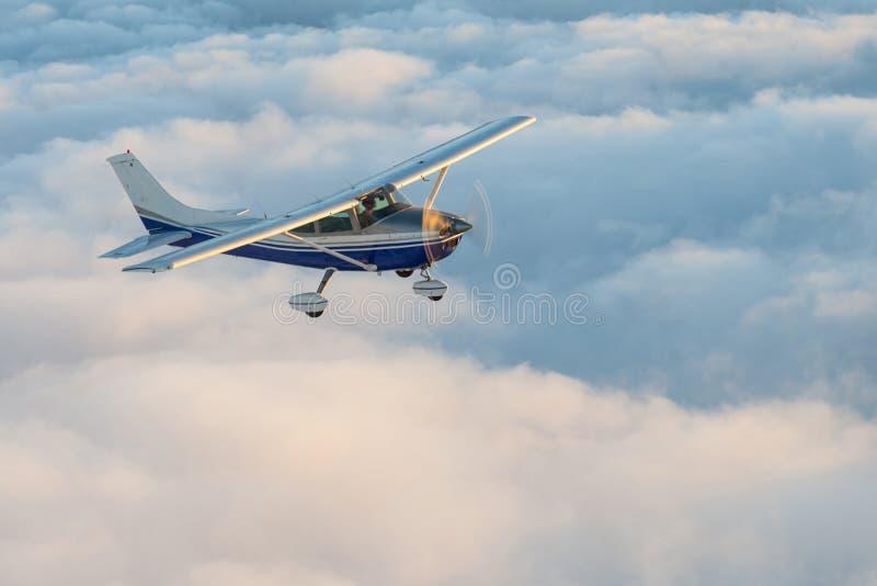 浏览在蓬松童话当中云彩的一架蓝色和白色矮小的私有赛斯纳飞机的惊人视图天空 免版税库存照片