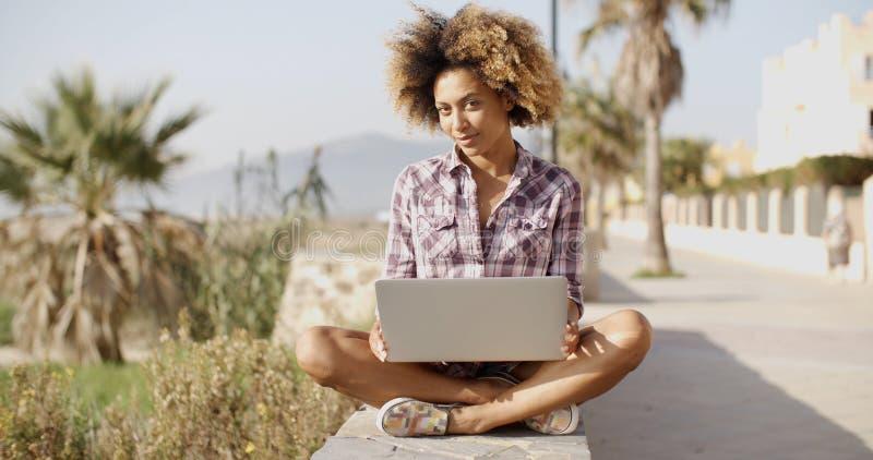 浏览在长凳的女孩一台膝上型计算机 免版税图库摄影