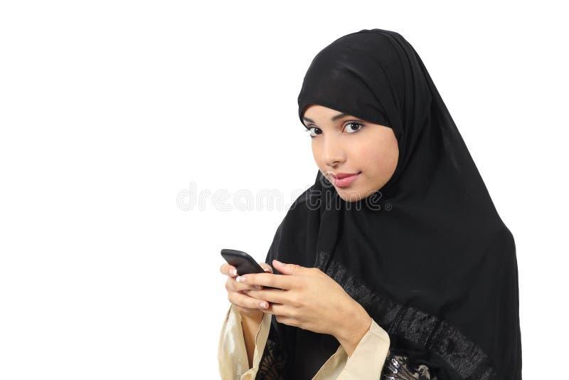 浏览她巧妙的电话和看对照相机的美丽的阿拉伯妇女 免版税图库摄影