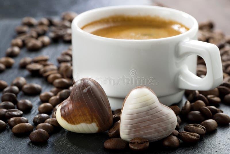 浓咖啡、咖啡豆和巧克力糖在心脏塑造 免版税库存照片