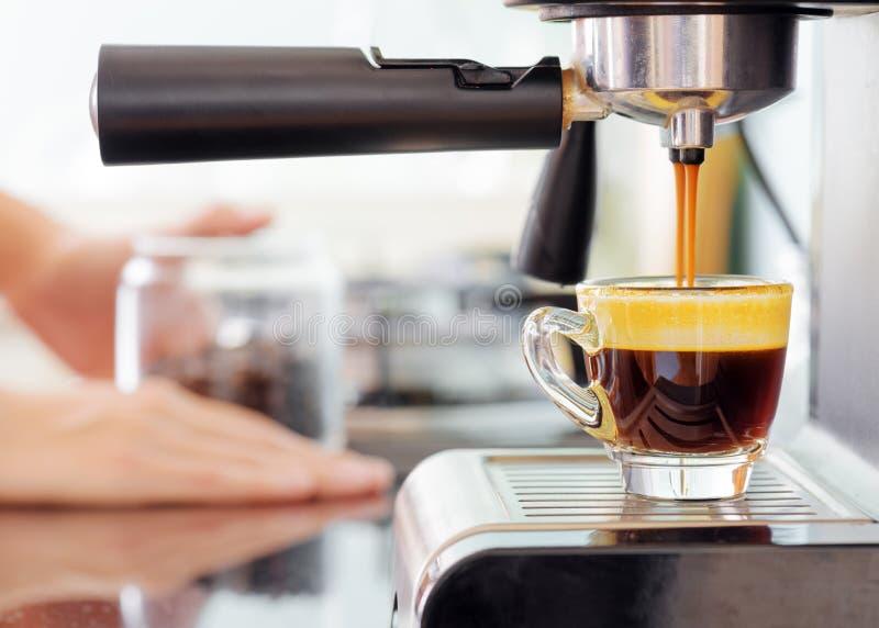 浓咖啡咖啡机器在厨房里 涌入杯子的热的咖啡 库存照片
