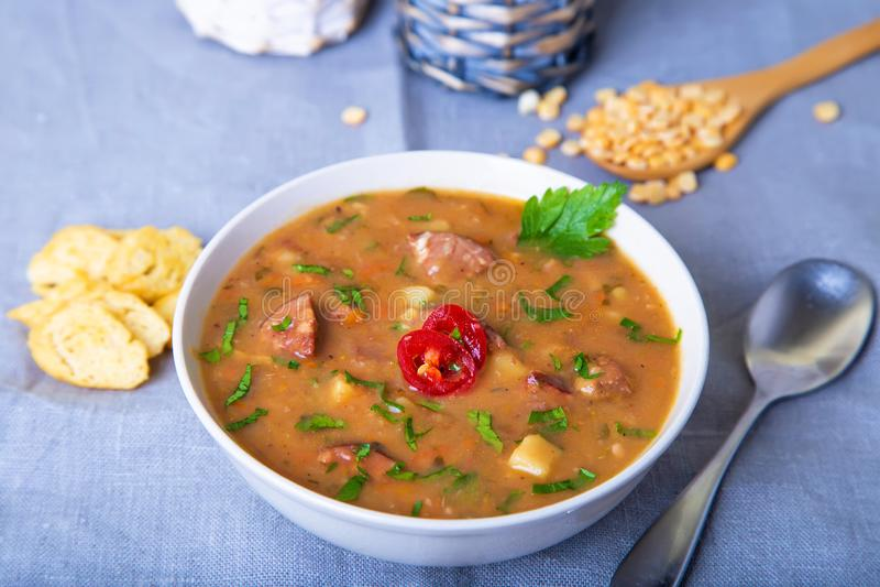 浓豌豆汤用肉、熏制的香肠和油煎方型小面包片 图库摄影