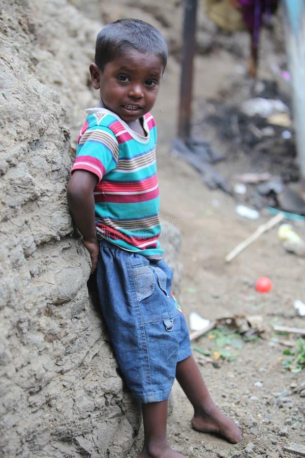 浦那,印度- 2015年7月16日:站立在骗局的一个可怜的印地安男孩 免版税库存图片
