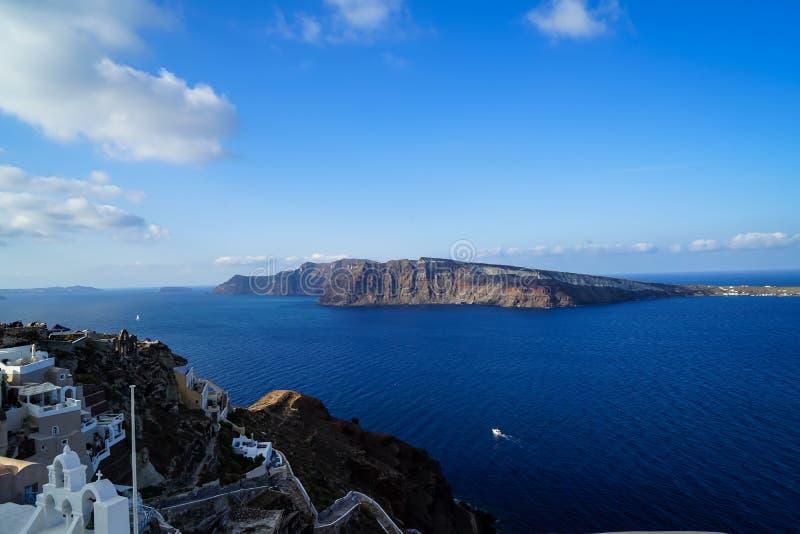 浩大的蓝色爱琴海、帆船和自然破火山口山美好的全景从Oia村庄有白色大厦的 免版税图库摄影