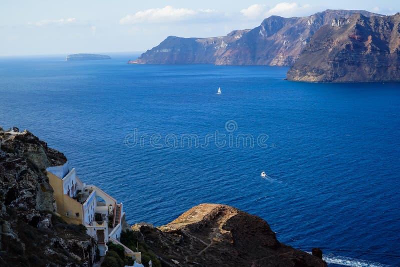 浩大的蓝色爱琴海海景和破火山口沿海岛前景的背景和大厦全景与帆船的从Oia 库存照片