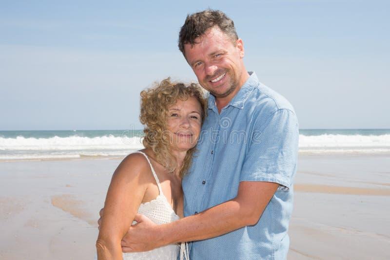 浪漫享受在海滩的中世纪夫妇美好的太阳步行 库存照片