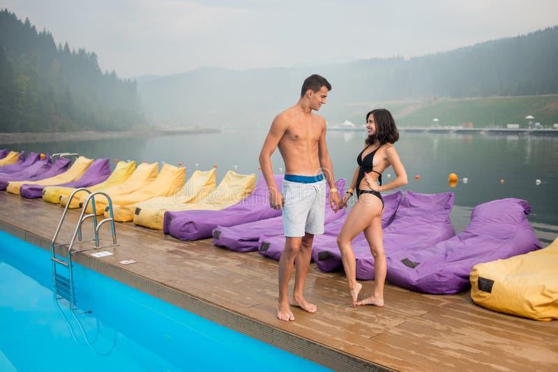 年轻浪漫加上站立近的游泳池的完善的身体 库存照片