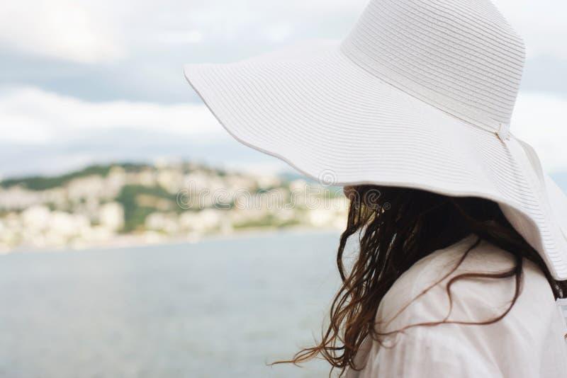 浪漫口气、妇女有白色帽子的和礼服在海边 库存图片
