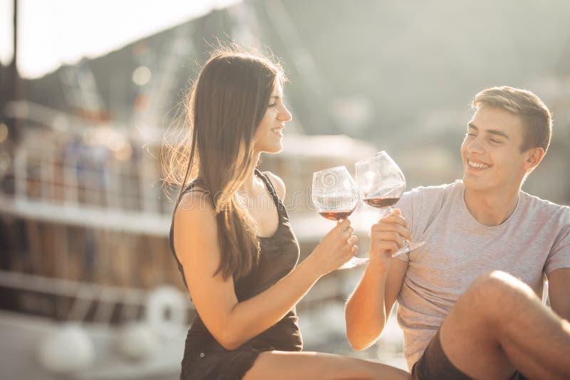 浪漫在日落的夫妇饮用的酒 言情 两个人有与一杯的一个浪漫晚上酒在海附近 肋前缘巡航luminosa船 库存图片