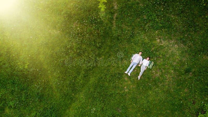浪漫在说谎在草的年轻人爱夫妇在公园举行手上从上面一起观看 免版税库存照片