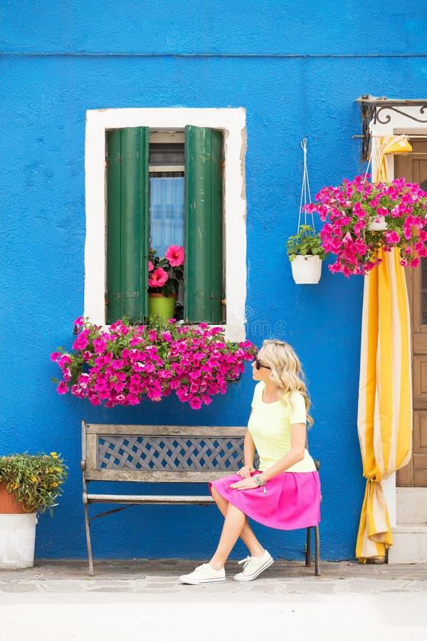 浪漫夫人坐在房子前面的长凳 免版税图库摄影