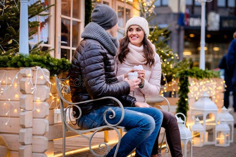 浪漫夫妇佩带的衣服暖和坐在平衡用美好的光装饰的街道的一条长凳,谈话和 免版税库存照片