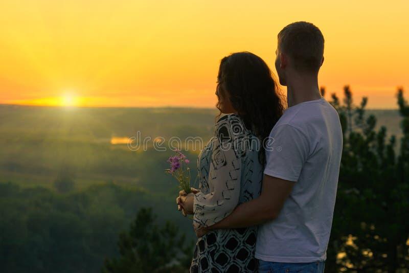 浪漫夫妇在太阳看,在室外,美好的风景和明亮的黄色天空,爱柔软概念,年轻成人p 库存照片
