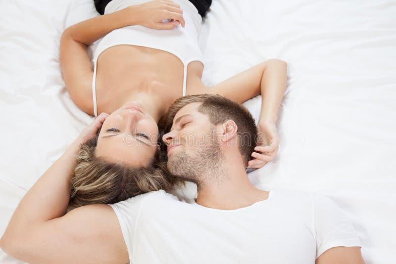 年轻浪漫夫妇在床上 免版税库存图片