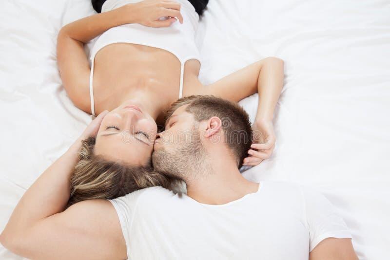 年轻浪漫夫妇在床上 库存图片