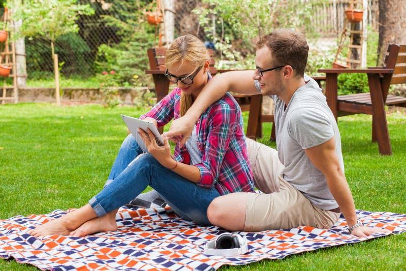浪漫夫妇坐有片剂个人计算机的一条毯子在夏天gr 图库摄影