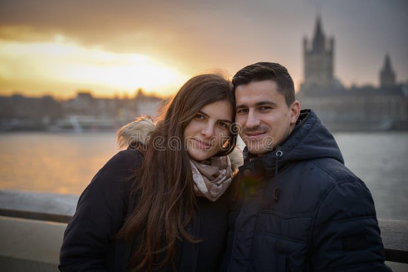 浪漫夫妇坐桥梁在日落 免版税库存照片