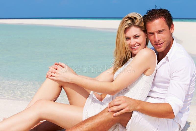 浪漫夫妇坐美丽的热带海滩 免版税图库摄影