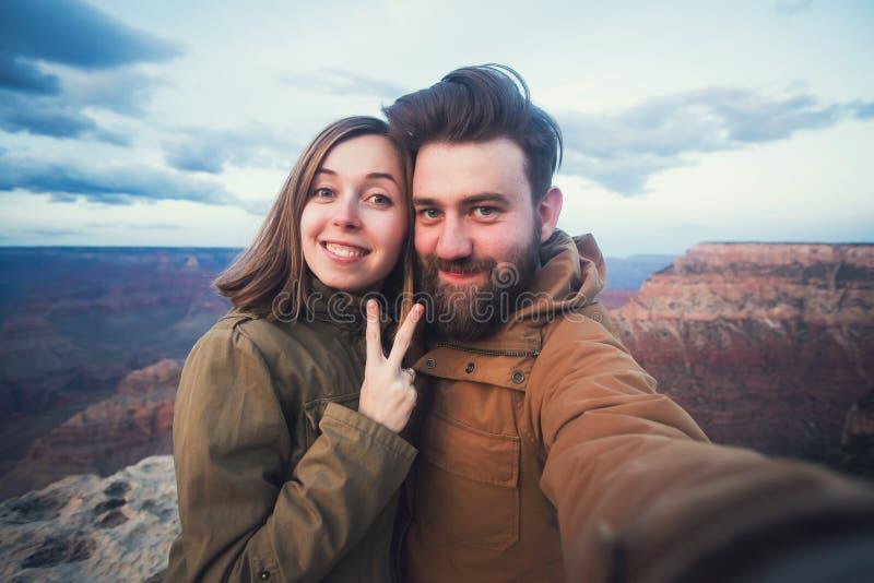 浪漫夫妇或朋友在亚利桑那显示赞许并且做selfie照片在远足在大峡谷的旅行 免版税库存照片