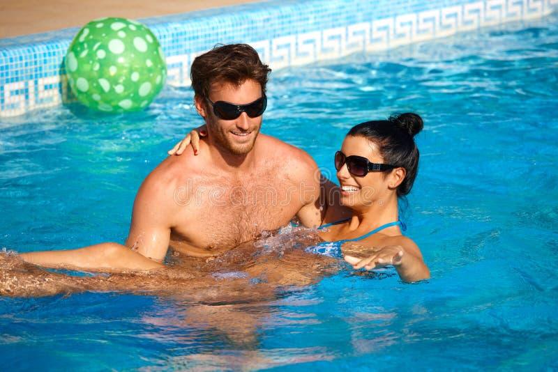 浪漫夫妇获得乐趣在游泳池 免版税库存图片