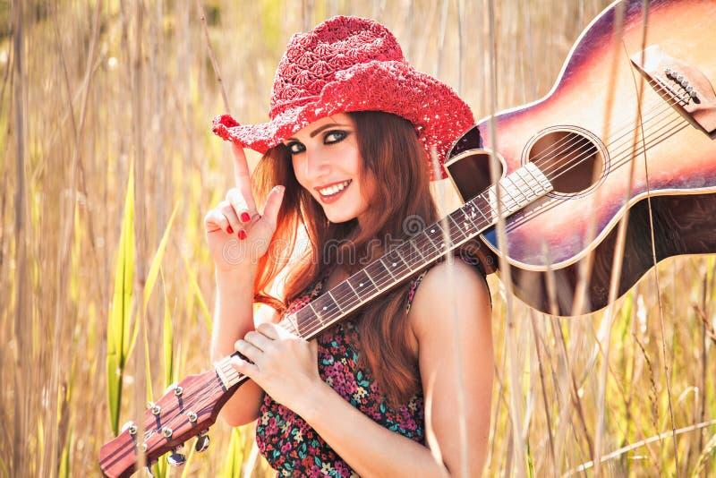 浪漫女孩和吉他 美好的礼服方式开花绿色嬉皮长的和平春天样式妇女年轻人 免版税库存图片