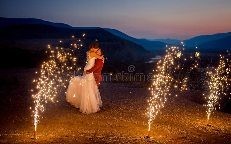 浪漫婚礼被射击亲吻的新婚佳偶 新郎举山的新娘装饰与 库存照片