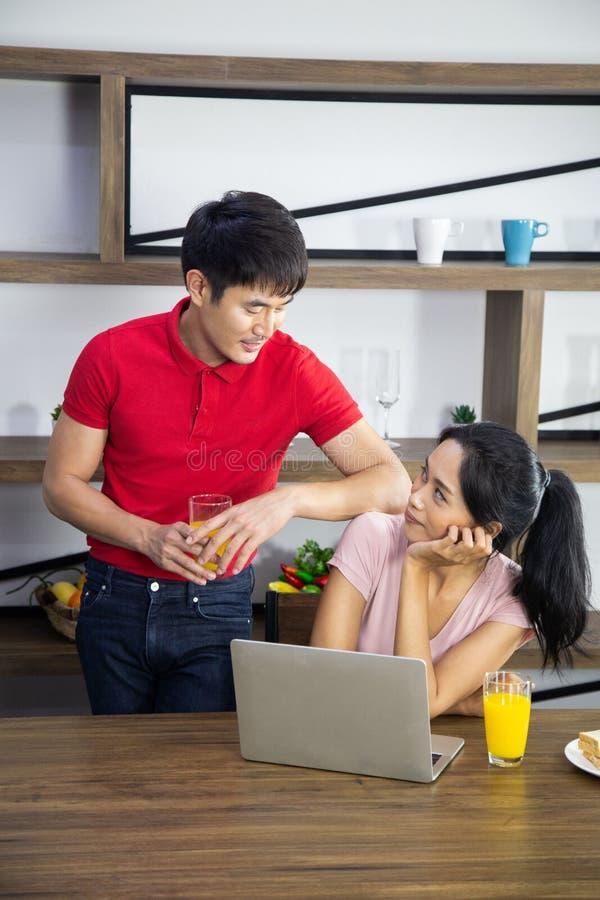 浪漫年轻可爱的夫妇饮用的橙汁过去和吃三明治在厨房里 库存照片
