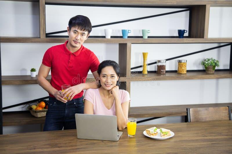 浪漫年轻可爱的夫妇饮用的橙汁过去和吃三明治在厨房里 图库摄影