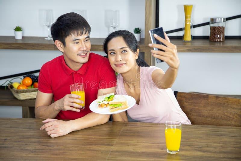 浪漫年轻可爱的夫妇selfie展示三明治在厨房里 库存图片