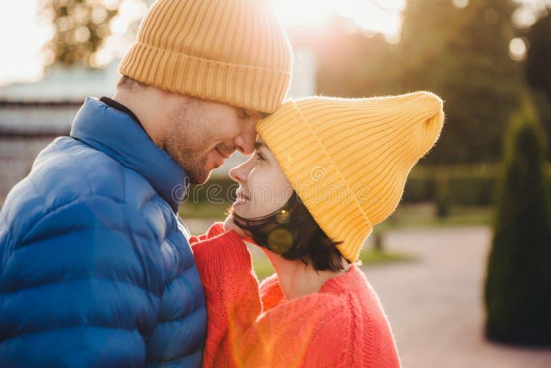 浪漫年轻夫妇看彼此充满巨大爱,有好的关系,去亲吻,有室外的步行在公园,穿戴w 免版税图库摄影