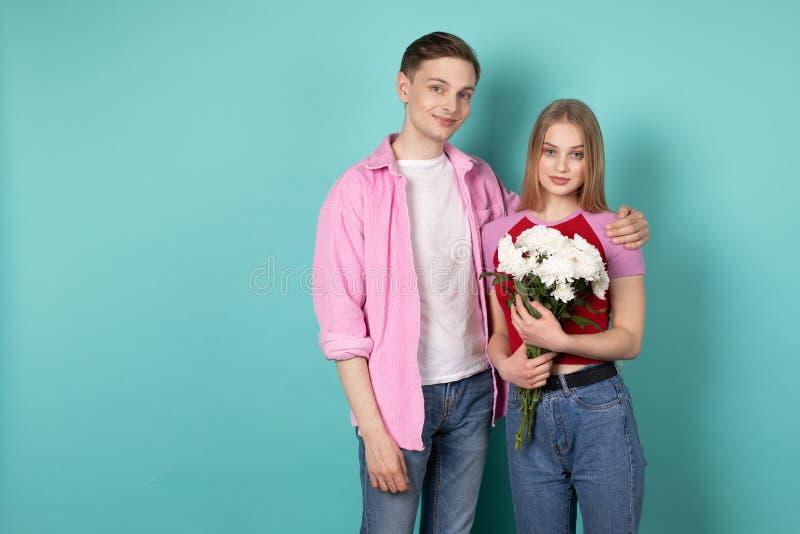 浪漫年轻夫妇,桃红色衬衣的帅哥有美丽的快乐的白肤金发的女孩的 免版税库存图片