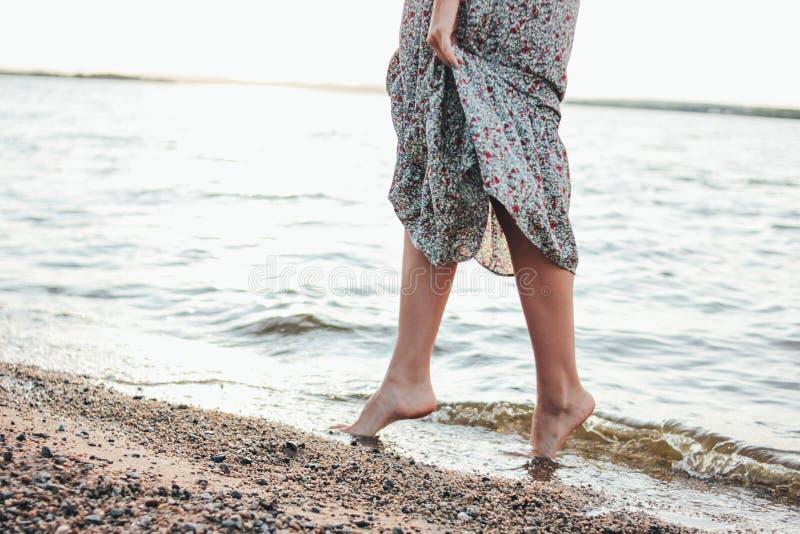 浪漫年轻女人的腿庄稼照片礼服的在海滩,暑假时间 免版税库存照片