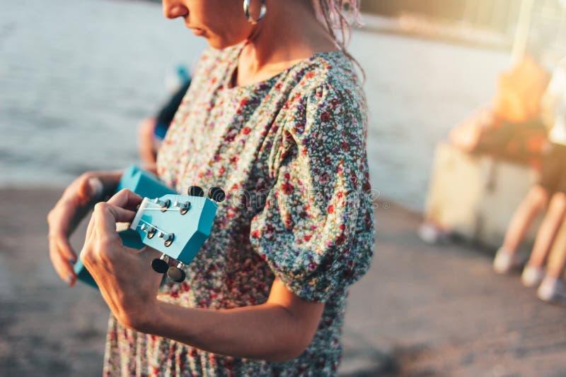 浪漫年轻女人音乐家庄稼照片有非洲辫子的在使用在日落海滩的尤克里里琴的礼服 库存照片